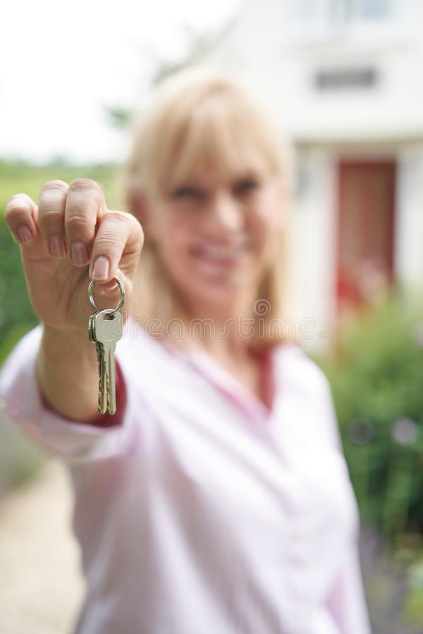 Portrait Of Mature Woman Standing In Garden In Front Of Dream Home In Countryside Holding Keys. Portrait Of Mature Woman Standing In Garden In Front Of Home In stock photography