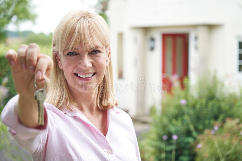 Portrait Of Mature Woman Standing In Garden In Front Of Dream Home In Countryside Holding Keys. Mature Woman Standing In Garden In Front Of Dream Home In royalty free stock photos