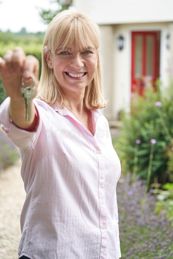 Portrait Of Mature Woman Standing In Garden In Front Of Dream Home In Countryside Holding Keys. Mature Woman Standing In Garden In Front Of Dream Home In royalty free stock image