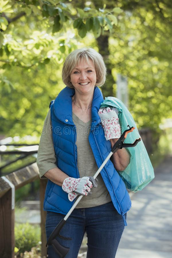 Mature Female City Cleaner. A portrait of a mature woman standing in a park, participating in a city clean up royalty free stock image