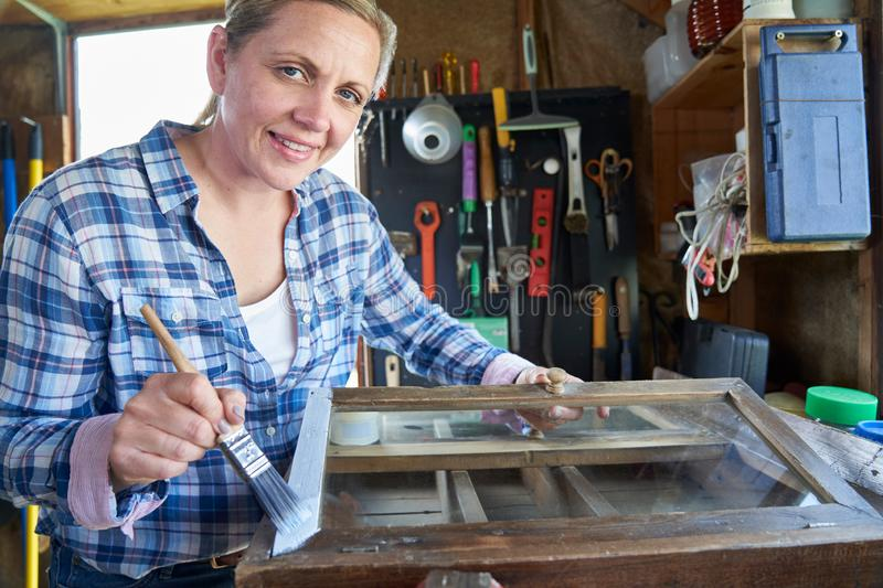 Portrait Of Mature Woman Upcycling Furniture In Workshop At Home Painting Cabinet. Portrait Of Smiling Mature Woman Upcycling Furniture In Workshop At Home stock images