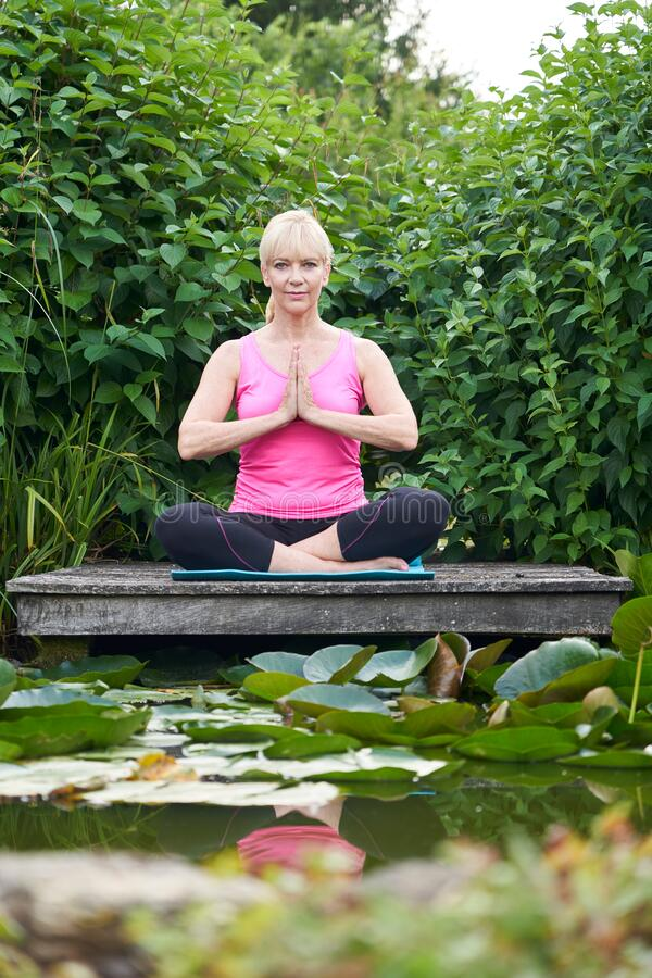Portrait Of Mature Woman In Yoga Position On Wooden Jetty By Lake Meditating stock image