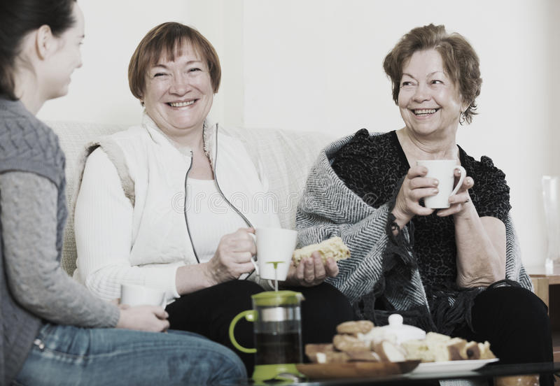 Portrait of mature and young women with tea. Portrait of mature and young women drinking tea and laughing royalty free stock photos