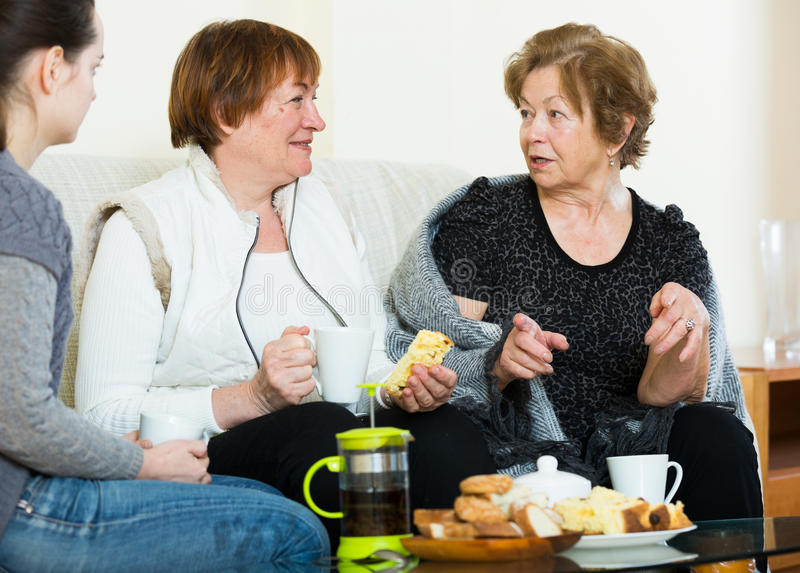 Portrait of mature and young women with tea. Portrait of mature and young women drinking tea and laughing stock photos