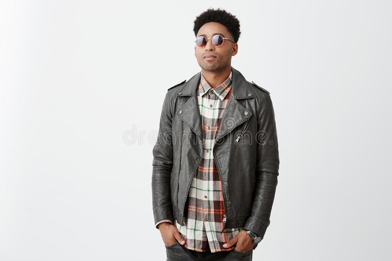 Portrait of mean good-looking dark-skinned guy with afro hairstyle in checkered shirt under leather jacket and royalty free stock images