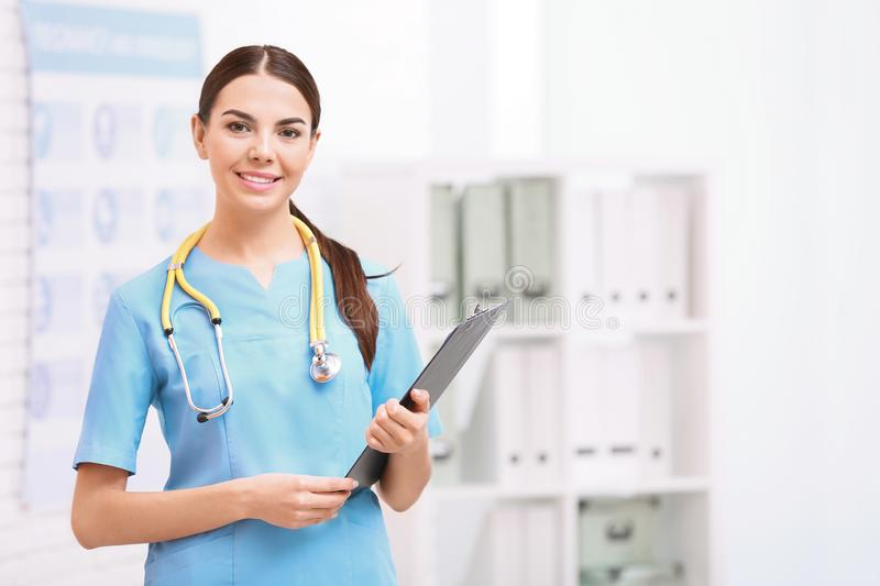 Portrait of medical assistant with stethoscope and clipboard in hospital. Space for text royalty free stock photography
