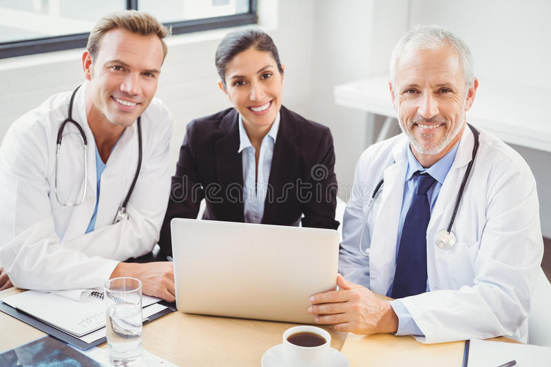 Portrait of medical team with laptop in conference room. Portrait of happy medical team with laptop in conference room in hospital stock images
