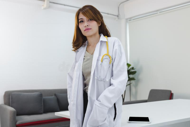 Portrait of medicine young Asian female doctor standing on workplace of hospital office. stock photos