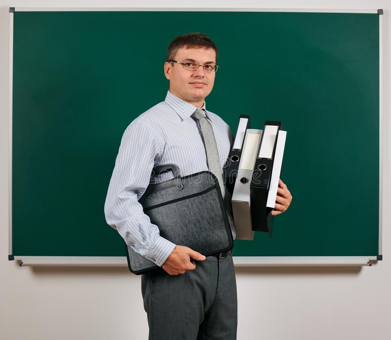 Portrait of a men dressed in business suit with folders, documents and briefcase, posing at blackboard background - learning and. Portrait of a man dressed in royalty free stock photo