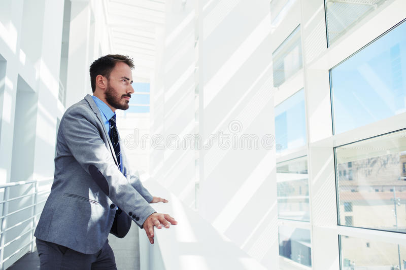 Portrait of a men entrepreneur dressed in expensive lux ury clothes looking in office window while rest after briefing. Intelligent male managing director royalty free stock images