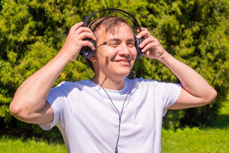 Portrait of men in headphones, in white T-shirt standing outside in park stock photos