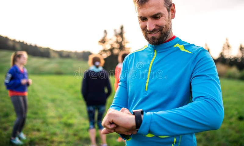 A portrait of man with large group of people doing exercise in nature. royalty free stock photos