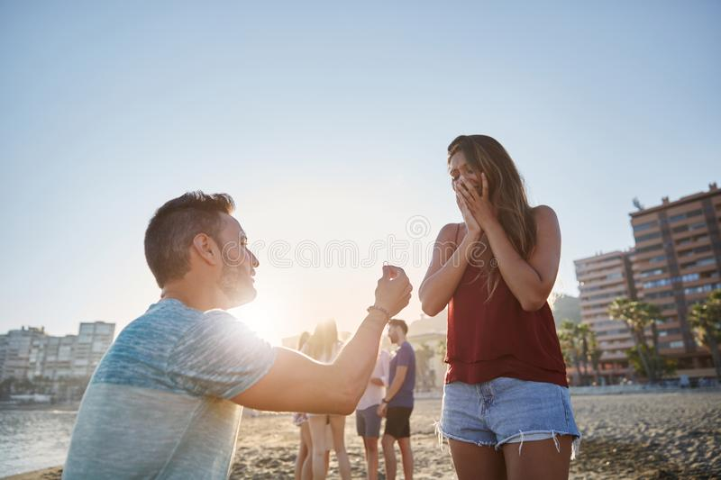 Man proposing to his girlfriend on beach in sunlight. Portrait of men proposing to his girlfriend on beach in sunlight royalty free stock photos