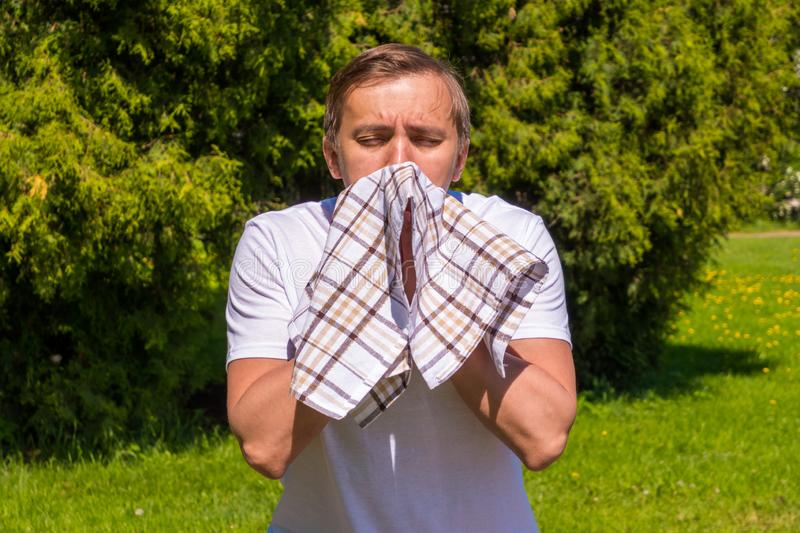 Portrait of men sneezing from allergy, in a white T-shirt, stands in the park stock photo