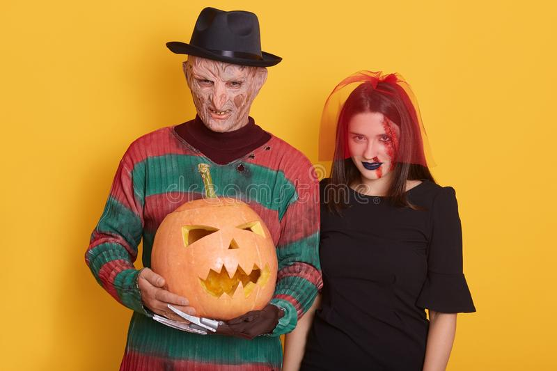 Portrait of man and woman with halloween pumpkin against yellow studio background, male with knives instead of fingers and female royalty free stock photos