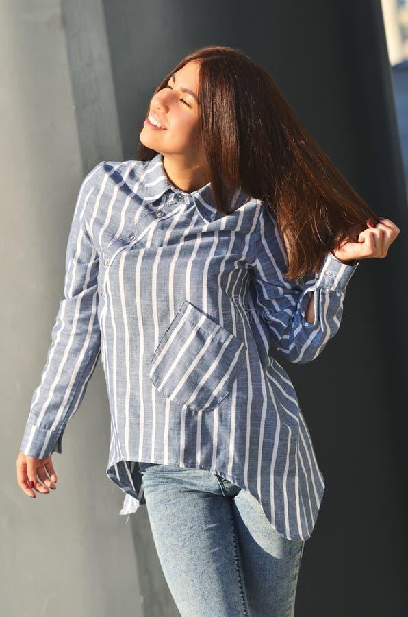 Portrait& x27; a menina asi?tica fresca nova de s est? perto da parede e levantar e vestiram uma camisa listrada imagem de stock