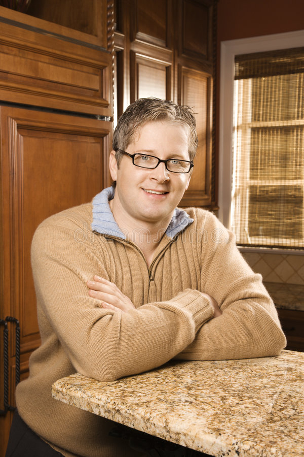 Portrait of mid-adult male in kitchen. stock photo