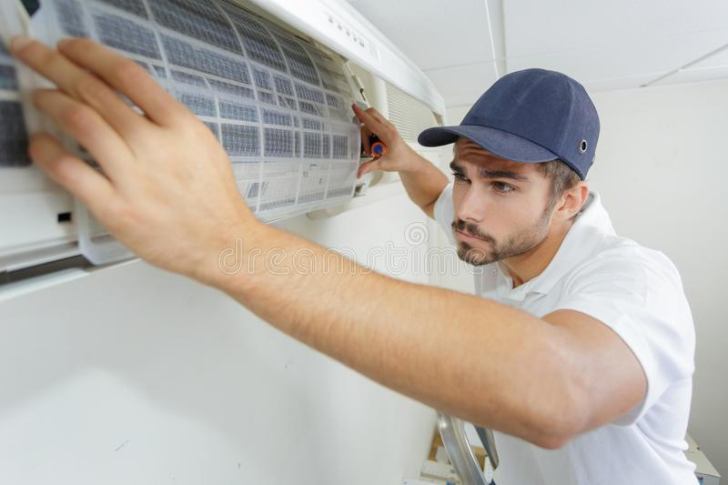Portrait mid-adult male technician repairing air conditioner royalty free stock images