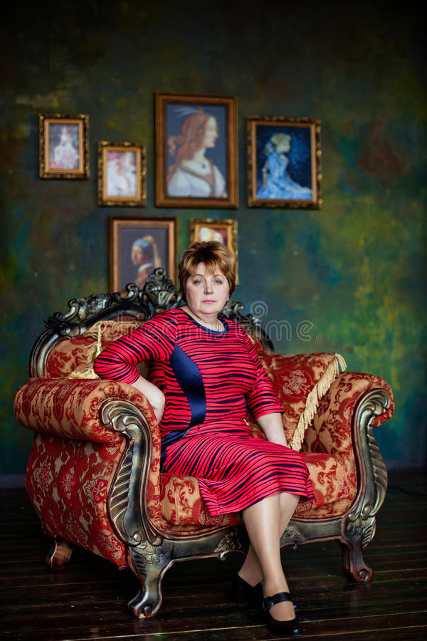 Portrait of mid-adult woman looking at camera sitting in armchair royalty free stock images