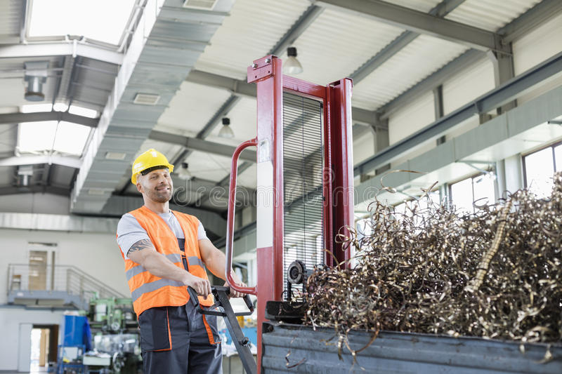 Portrait of mid adult worker pulling hand truck loaded with steel shavings in factory stock photography