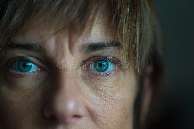 Portrait of mid aged woman with blue eyes, close up and selective focus on one eye, very shallow depth of field. Dark setting, ton royalty free stock photo