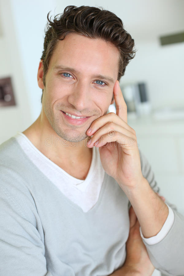 Portrait of middel-aged man smiling at camera. Smiling handsome guy with hand on chin royalty free stock image