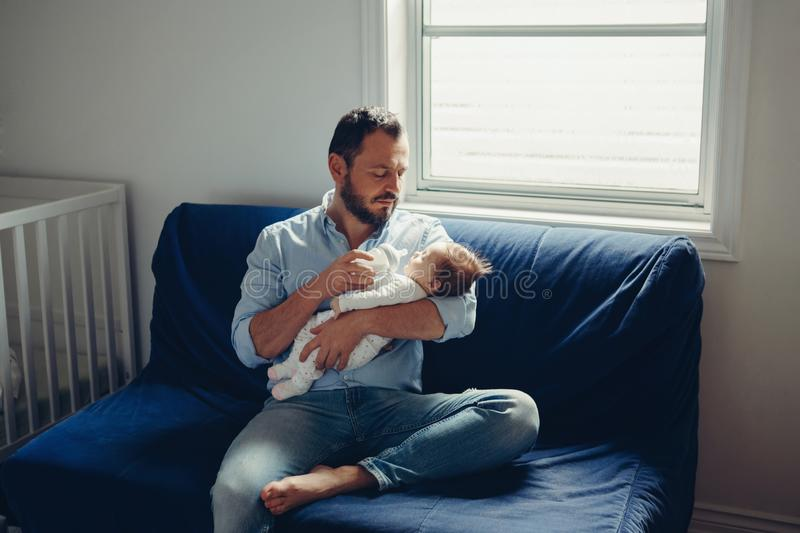 Caucasian father feeding newborn baby son daughter with milk royalty free stock photo