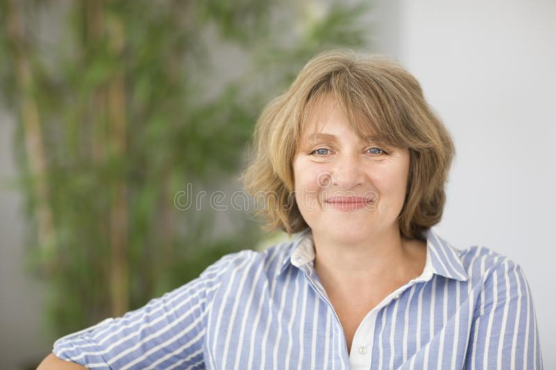 Portrait of middle age woman in the room. Portrait of smiling blonde middle age woman in the room royalty free stock photography