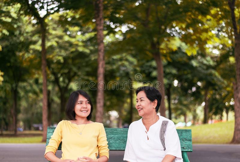Portrait of middle aged Asian woman with daughter talking together at outdoor,Happy and smiling,Positive thinking,Take care and s stock image