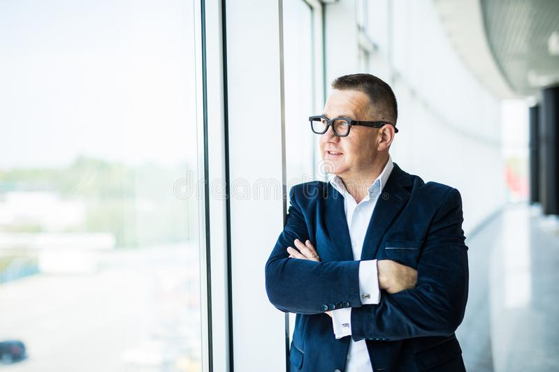 Portrait of a middle aged businessman in front of office window. Man is smiling and has his arms folded. stock images
