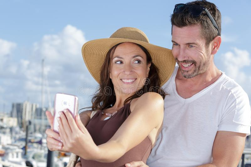 Portrait middle-aged couple taking selfie with smartphone royalty free stock photography