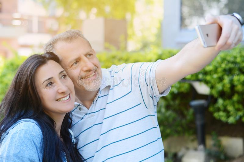 Portrait of middle-aged couple taking selfie with a smartphone royalty free stock photo