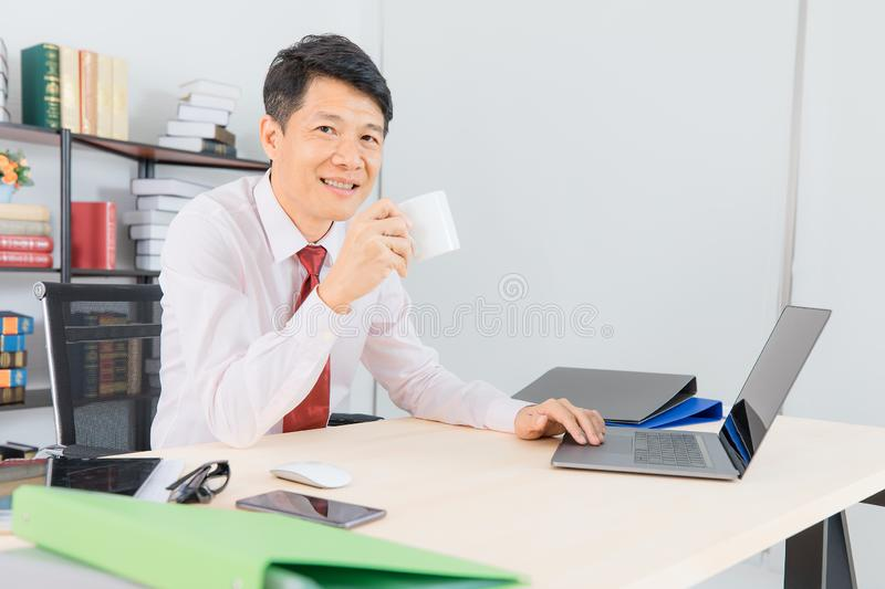 Asian business man at office. Portrait of Middle aged, handsome, Asian, businessman, in white shirt, dark red necktie, working in his startup office, happy with stock images