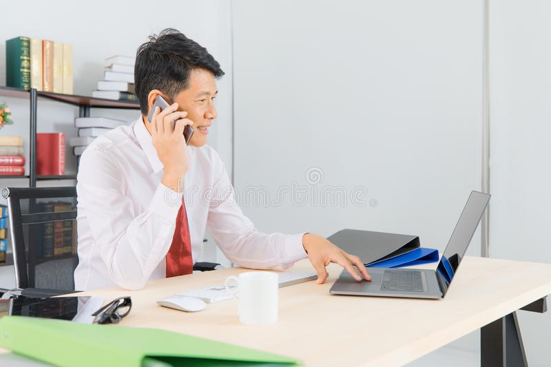 Asian business man at office. Portrait of Middle aged, handsome, Asian, businessman, in white shirt, dark red necktie, working in his startup office, talking on royalty free stock photography