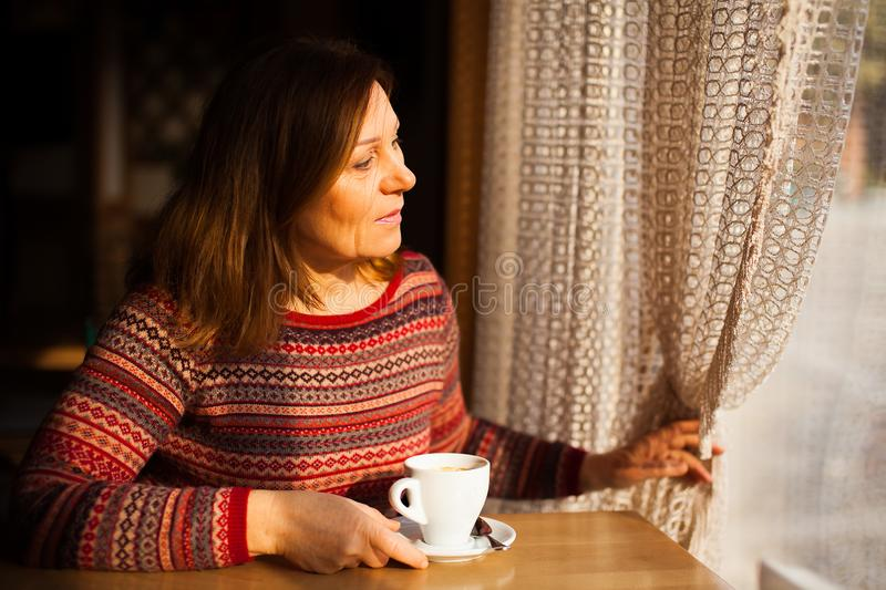 Middle aged lady in striped sweater looking throught the window with a cup of coffee royalty free stock images