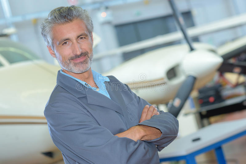 Portrait middle aged man in aircraft hangar. Portrait of middle aged man in aircraft hangar royalty free stock photos