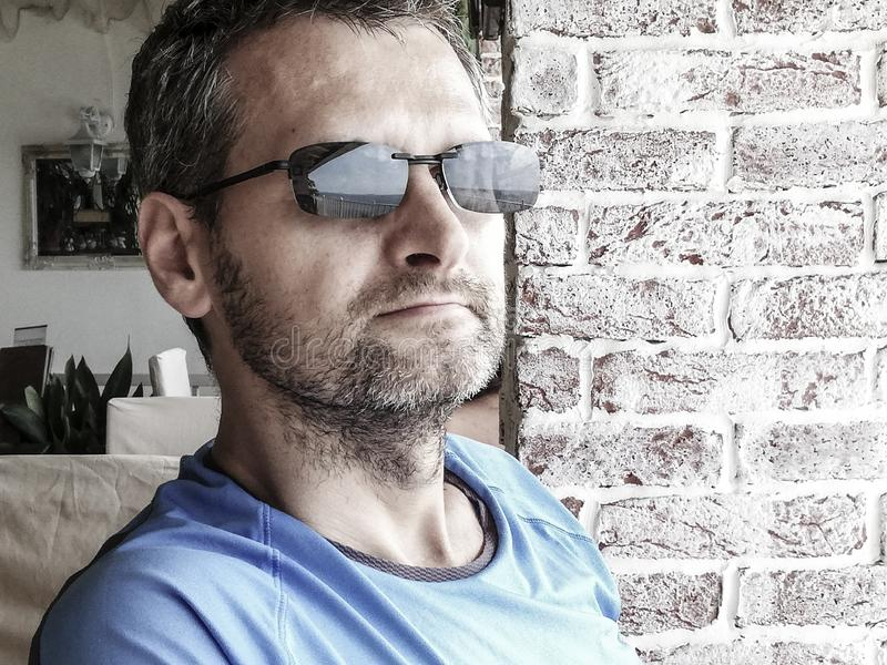 A middle aged man in sunglasses, close-up. A portrait of a middle aged man in a blue t-shirt and sunglasses relaxing in a cafe looking at the sea reflected in royalty free stock photos