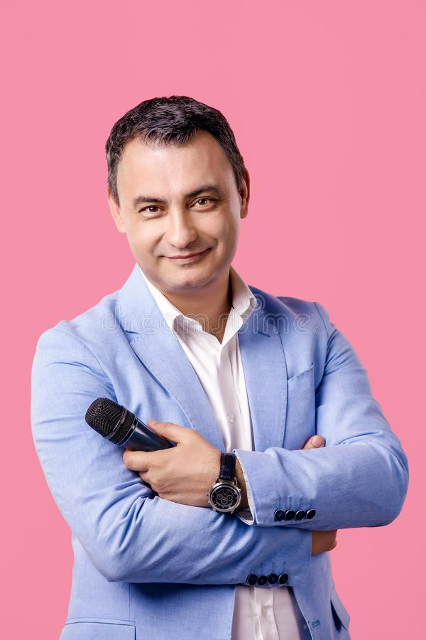 Portrait of middle aged man with microphone in hand wearing blue jacket. smiling. isolated pink background stock photo