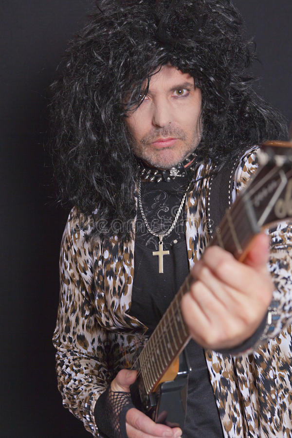 Portrait of middle-aged man wearing leopard skin pattern with guitar over black background royalty free stock photo