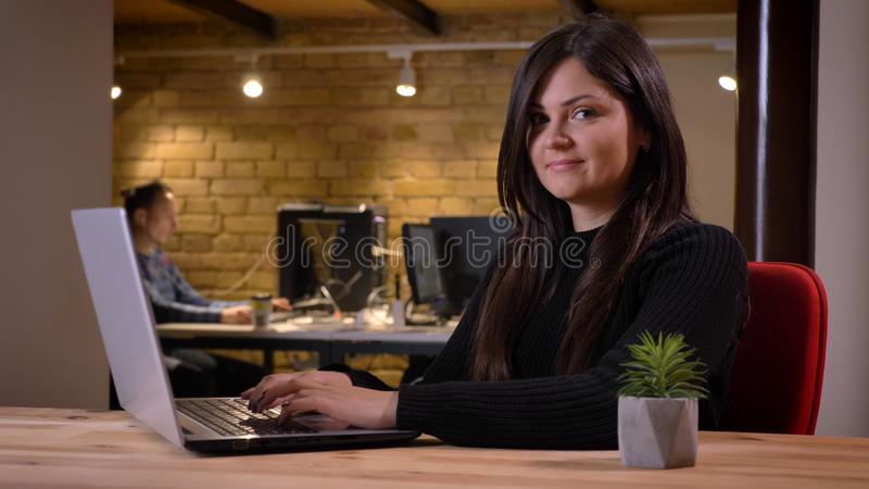 Portrait of middle-aged overweight businesswoman sitting in front of laptop and smiling into camera on office background royalty free stock photography