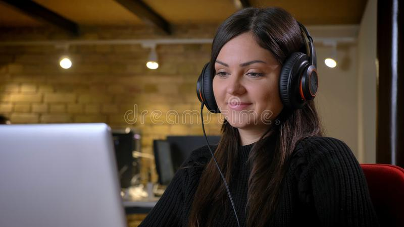Portrait of middle-aged overweight woman in headphones watching into laptop smilingly on office background. stock photography