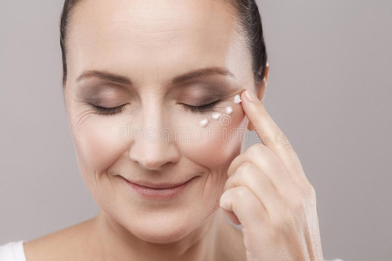 Portrait of middle aged woman with perfect face skin applying cosmetic cream on skin near eyes with closed eyes isolated on grey royalty free stock image