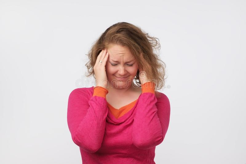 Portrait of middle aged woman in pink sweater isolated on grey background suffering from severe headache stock images