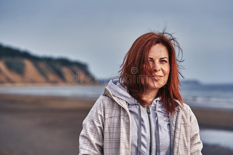Portrait of a middle-aged woman with red hair walking along the river bank. Sunny spring morning. Close-up stock image