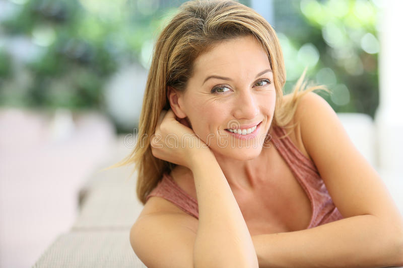 Portrait of middle aged woman relaxing on sofa royalty free stock photos