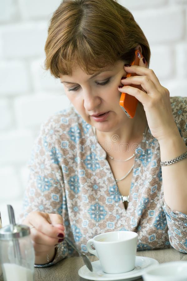 Portrait of a middle-aged woman talking on the phone. Close-up stock photography