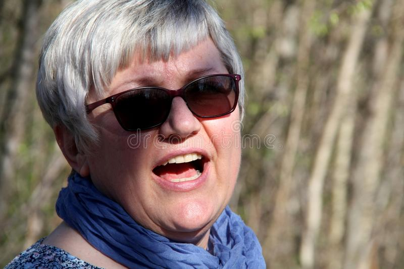 Portrait of a middle-aged woman through the walk in nature talking. Portrait of a middle-aged woman through the walk in nature with sunglasses, talking in a royalty free stock images