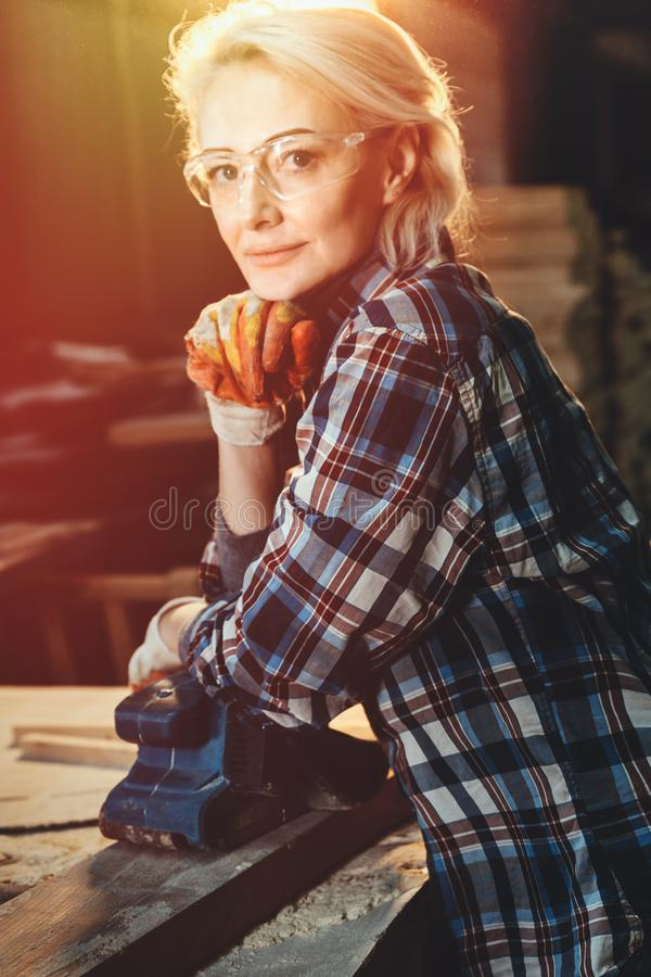 Portrait of middle aged woman worker posing near woodworking workshop. Concept of motivated women, gender equality, image of royalty free stock images