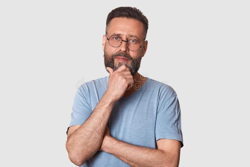 Portrait of middle bearded aged male with pensive facial expression, dressed gray cassual t shirt and round spectacles, keeps hand royalty free stock photo