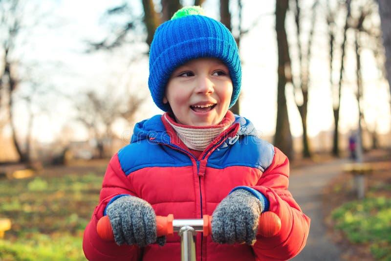 Portrait mignon d'extérieur de petit garçon L'enfant heureux dans des vêtements chauds monte le scooter au parc d'automne Enfance images libres de droits